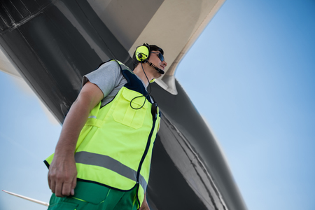 Nice view. Low angle portrait of serene man in headset. Blue sky and giant plane on background