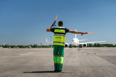Time for landing. Aviation marshaller meeting passenger plane at the airport