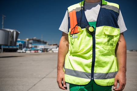 Work clothing. Close up of male torso in signaling vest. Airport terminal, runway and blue sky on blurred background Imagens