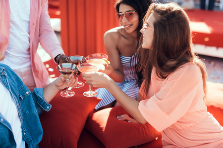 Outgoing women clanging glasses of cocktail with males during positive conversation. Satisfied comrades during rest concept Фото со стока