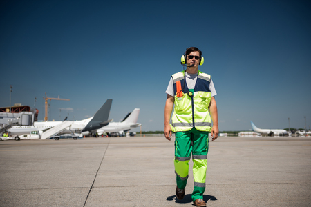 I am coming. Full length portrait of aviation marshaller walking down the runway. Man wearing sunglasses and headphones Stock Photo