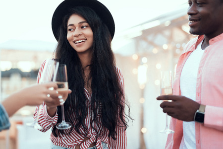 Satisfied woman talking with cheerful comrades while enjoying appetizing glass of alcohol liquid during party