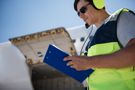 Noting all details. Low angle portrait of airport worker filling out documents. Open cargo door on blurred background Stock Photo