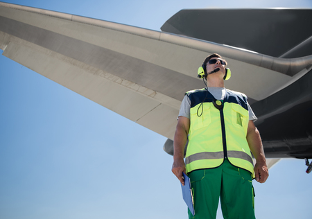 Beautiful view. Low angle portrait of airport worker. Man holding clipboard and looking up with calmness