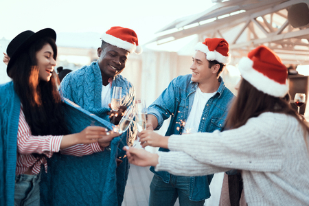 Positive women and smiling men clanging glasses of champagne while communicating during party. Glad comrades having fun during christmas concept