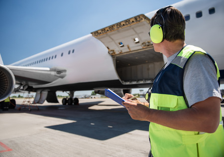 Aircraft ground handling. Man in headphones observing airplane with open cargo door and intending to fill out documents. Copy space in left side 写真素材