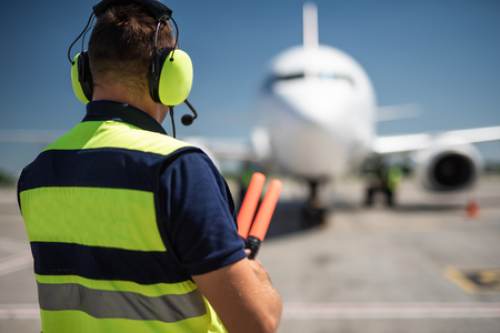 Meeting aircraft. Back view of aviation marshaller observing commercial jet and waiting for signaling Imagens - 106442810