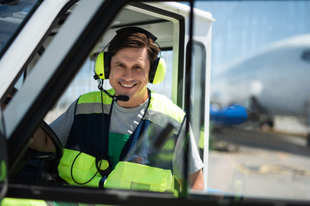 Love my job. Waist up portrait of cheerful man in headphones sitting behind the wheel. Airplane on blurred background