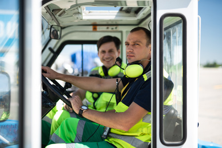 Photoshoot during work. Serious man in headphones with microphone sitting behind the wheel. Smiling colleague on blurred background
