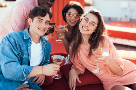 Satisfied males and beaming women drinking alcohol cocktails while looking at camera. Cheerful comrades relaxing together concept Фото со стока