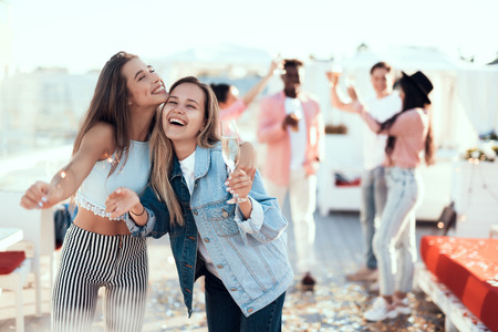 Portrait of cheerful girl embracing glad woman. They holding firework sparklers in arms. Satisfied comrade tasting appetizing liquid