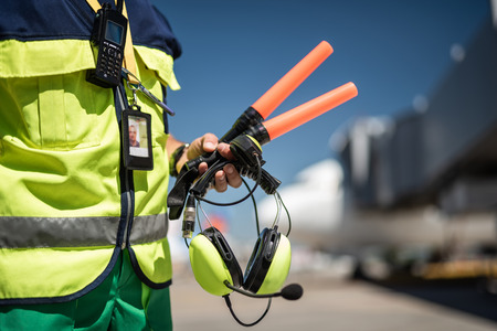 Waiting for plane. Close up of airport worker torso in vest and arm with headset. Airdrome on blurred background Stock fotó - 106442894