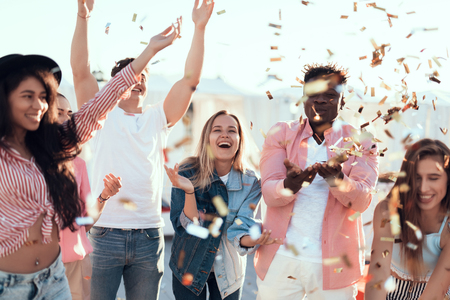 Outgoing males and cheerful women throwing confetti having fun outdoor. Positive comrades spending time together concept