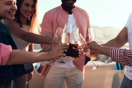 Cheerful girls and beaming men drinking alcohol liquid while locating outdoor during party