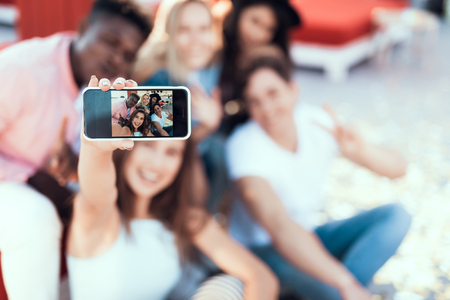 Close up girl hand holding phone. Cheerful friends doing photo on it Banco de Imagens