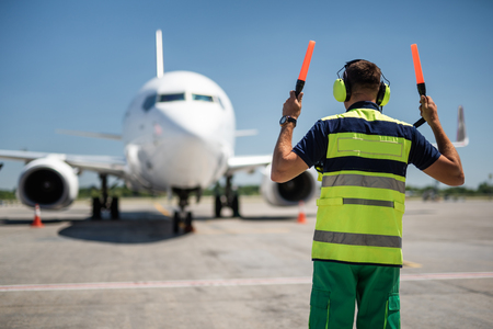 Welcome home. Back view of aviation marshaller directing aircraft landing