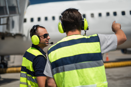 Telling jokes at work. Cheerful technician in sunglasses looking at friend. Man in headphones pointing at passenger plane Stock Photo