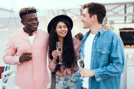 Happy male embracing cheerful woman while telling with satisfied comrade. They tasting appetizing alcohol liquid. Glad friends during party concept