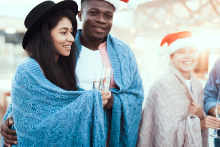 Are you chilly. Positive young male embracing outgoing pretty lady during party. She wearing plaid. They tasting alcohol beverage. Cheerful couple celebrating christmas concept