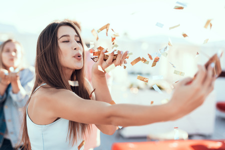 Portrait of happy pretty lady blowing confetti while keeping it in hands. She taking photo on modern gadget Stock Photo