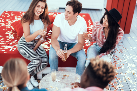 Top view beaming women telling with happy attractive man. They drinking bottle of beer and glasses of champagne