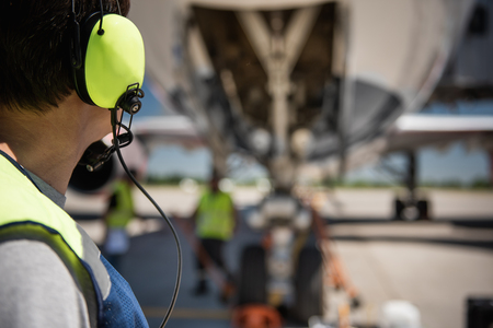 I see you. Close up back view of aviation marshaller isolated on blurred background. Copy space in right side