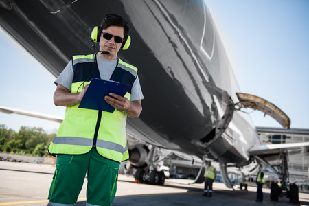 Active teamwork. Low angle portrait of serene man in sunglasses writing on clipboard. Colleagues, plane with open cargo door in the background