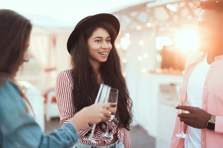 Portrait of outgoing pretty girl with attractive smile telling toast while clanging with cheerful friends during celebration Stock Photo