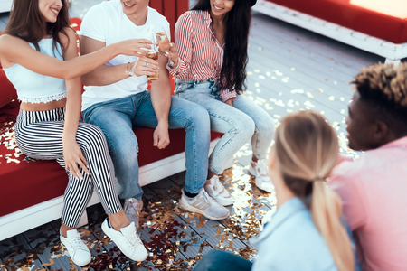 Happy ladies talking with outgoing men while sitting on cozy sofa. They drinking champagne and beer during conversation Stock Photo