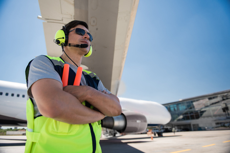 Staying positive. Low angle portrait of serene man standing at airport and looking away with half-smile