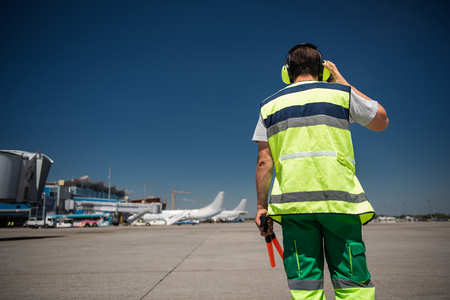 I hear you. Back view of man in signaling vest holding wands and checking the headset. Blue sky, runway, passenger planes and terminal on background