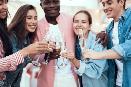 Outgoing men and cheerful females clanging glasses of champagne while speaking. Happy friends during party concept