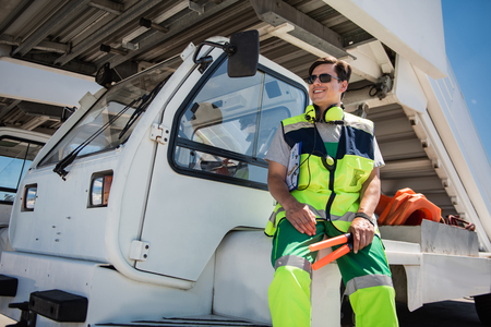 Feeling comfortable. Low angle portrait of cheerful aviation marshaller sitting on vehicle. Man holding signal wands and looking away Stock Photo