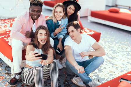 Portrait of satisfied young women and cheerful males taking selfie on mobile. Happy girl holding gadget in hands Stock Photo