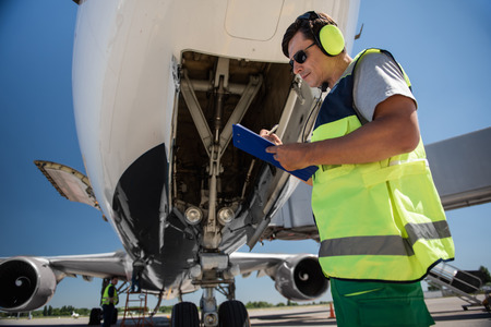 Doing paperwork. Low angle portrait of man in sunglasses writing on clipboard while standing near commercial jet with open door