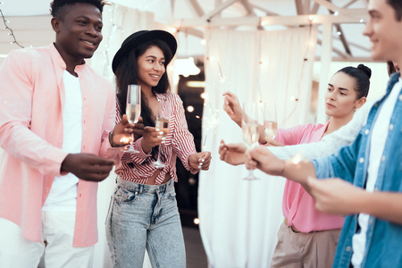 Outgoing girls holding firework sparklers while talking with cheerful men. They drinking glasses of champagne during party. They gesticulating hands