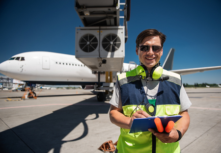 Doing job with joy. Cheerful man in sunglasses noting data and holding signal wands. Passenger plane on background Stock Photo