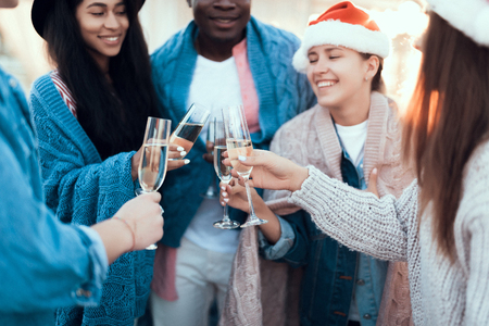 Satisfied women and cheerful men drinking glasses of delicious beverage while celebrating new year