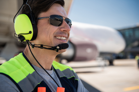 Feeling joyful. Close up portrait of cheerful man with wide smile. Passenger plane, blue sky and runway and blurred background