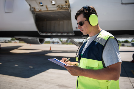 Important data. Side view of serene man in sunglasses and headphones filling out documents. Plane with open cargo door in the background Stock Photo