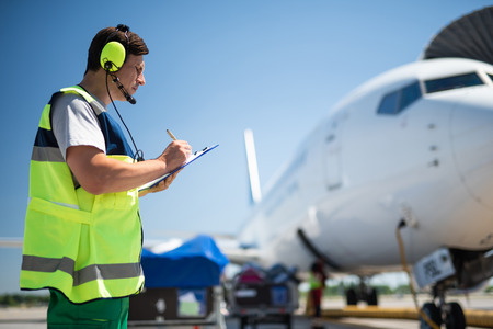 Being responsible at work. Side view of aviation technician noting data before the flight. Blue sky and passenger plane on blurred background