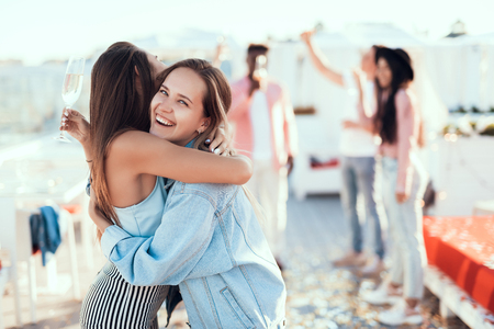 Beaming girls hugging while walking locating outdoor together. Glad friends concept