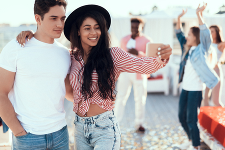 Portrait of positive girl embracing happy male while keeping mobile in hand. They taking selfie on appliance Stock Photo
