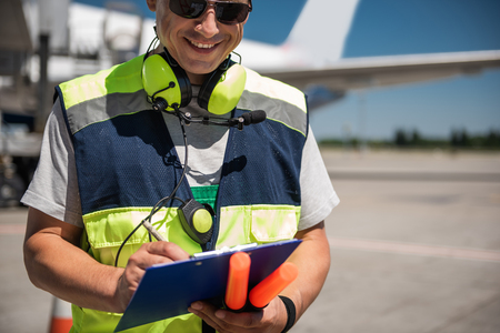 Feeling well. Smiling aviation marshaller noting data while holding signal wands. Runway and passenger plane on blurred background