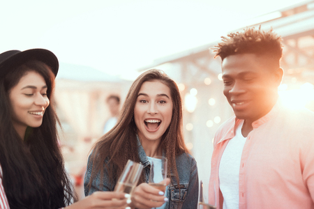 Portrait of positive girls and laughing man tasting alcohol beverage