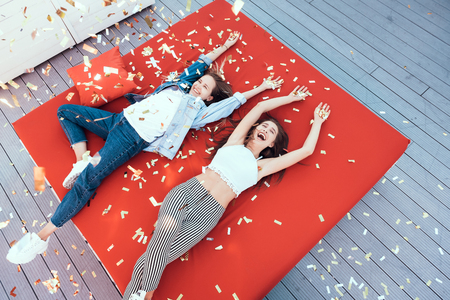 Top view portrait of two young laughing girls lying on cozy couch during conversation. Confetti locating on them