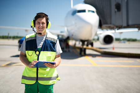 Doing job with joy. Cheerful man posing at airdrome. Passenger plane on blurred background