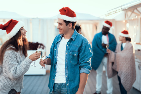 Side view outgoing man talking with beaming pretty girl. They tasting alcohol liquid during new year party Stock Photo