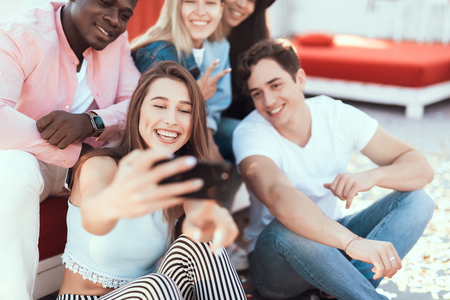 Beaming girl and happy men looking at display of modern phone while taking photo on appliance Stock Photo