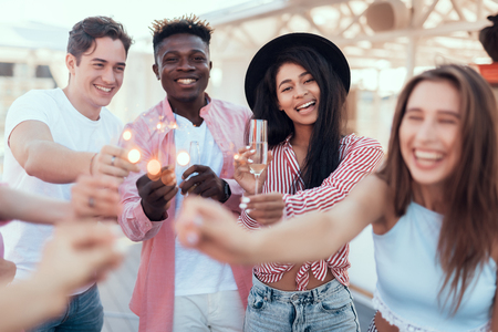 Portrait of laughing girls and cheerful men tasting appetizing alcohol liquid while holding bengal lights in arms